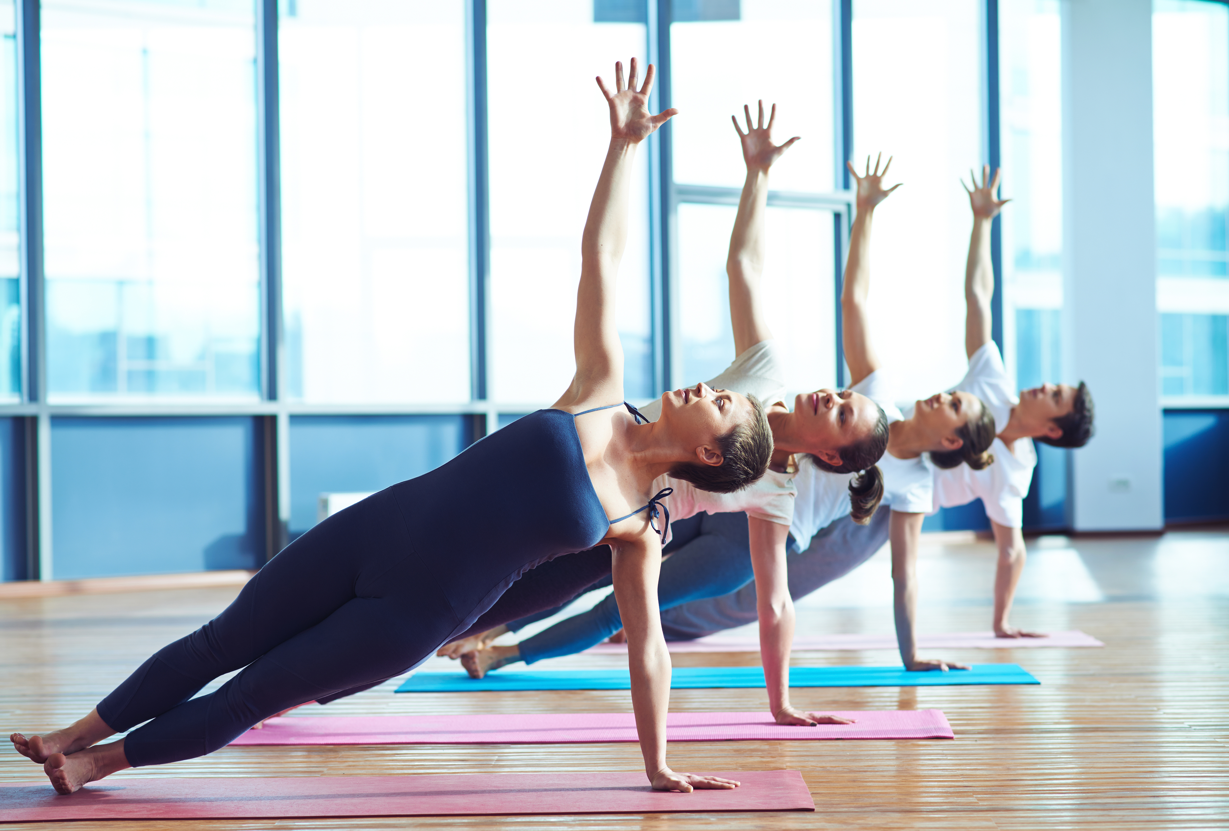 Group of young people practicing side plank pose during a class in gym