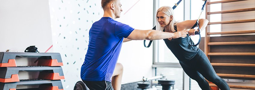woman-exercising-with-personal-trainer-at-the-gym-KSEW5Y25