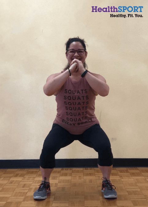 woman smiling performing squat exercise in a gym
