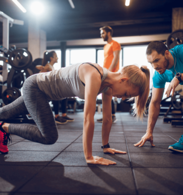 Personal trainer focusing on technique of the trainee while she does mountain climbers to strengthen her core in a gym.